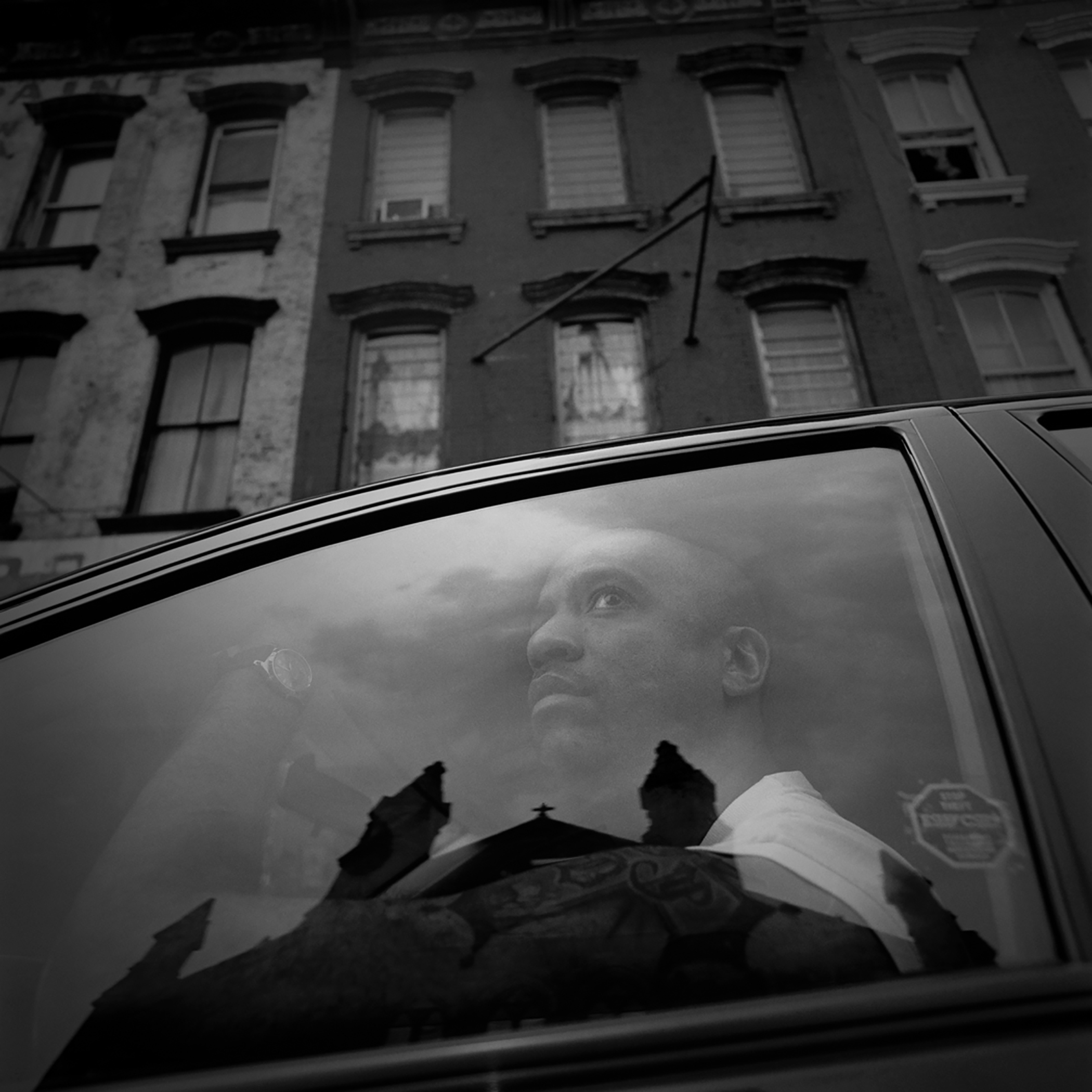 """# 2 of 3, from the book, """"Crosses: Portraits of Clergy Abuse"""", by photographer, Carmine Galasso.  06/26/2004.  Paterson, N. J.  """"I was raped by a priest and later by a deacon.  When you come down to it, that's what it was - brutal rape"""", says Johnny Vega a victim/survivor of clergy sexual abuse.  """"I still get intimidated by that church.  Even now I have dreams wondering if that door is going to open and see the priest."""" Mr. Vega summoned up the strength to drive past the church reflected in his car window, where he was brutally raped as a young boy by a Catholic priest.  Photo:  Carmine Galasso."""
